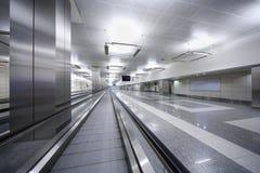 Långt hall med spåret för passagerare i flygplats. royaltyfri fotografi