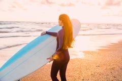 långt kvinnabarn för härligt hår Surfa flickan i wetsuit med surfingbrädan på en strand på solnedgången eller soluppgång Arkivfoton