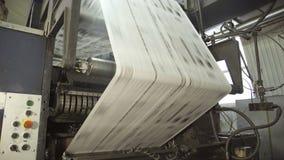 Långt oklippt papper på den rullande maskinen i printinghus lager videofilmer
