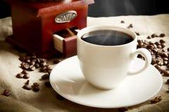 Långt skott av koppen kaffe, påse, kaffebönor på linlinne Arkivfoto