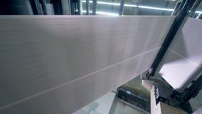 Långt tidningsark som går på en tryckkontorslinje, nedersta sikt