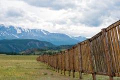 Långt trästaket i ett fält I avståndet bergen Arkivbilder