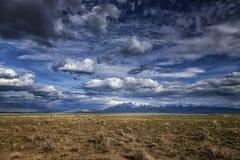 Långväga berg på en Prarie med moln arkivfoton