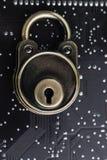 Låsblock på mörkt svart datorströmkretsbräde med lödmetall, safet arkivfoto
