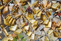 Låsen fästas till bron avbrott av glass mantraditionsbröllop Mycket guld- lås arkivfoton