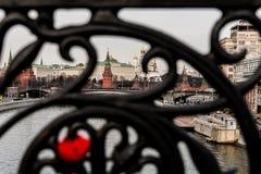 Låset på det falska gallret av bron är ut ur fokus och en härlig sikt av Kreml Arkivbilder
