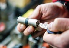 Låssmedförlagen reparerar cylindern för dörrlåset royaltyfri fotografi