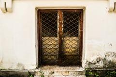 Låst dörr med järnstaketet som håller hemligheter inom grungebyggnaden i det förbjudna stället arkivfoto