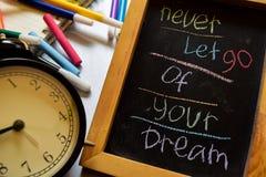 Låt aldrig går av din dröm på färgrikt handskrivet för uttryck på den svart tavlan, ringklockan med motivation och utbildningsbeg arkivbild