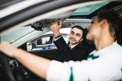 Låt mig visa dig inre av denna bil Stiligt ungt klassiskt bilförsäljareanseende i återförsäljaren och portionen en klient som ska arkivbild
