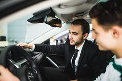 Låt mig visa dig inre av denna bil Stiligt ungt klassiskt bilförsäljareanseende i återförsäljaren och portionen en klient som ska arkivfoton