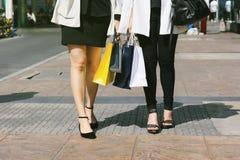 Låt ` s gå att shoppa, kvinnor som rymmer shoppingpåsar på gatan Royaltyfria Bilder