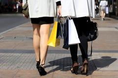 Låt ` s gå att shoppa, kvinnor som rymmer shoppingpåsar på gatan Royaltyfri Foto