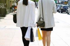 Låt ` s gå att shoppa, kvinnor som rymmer shoppingpåsar på gatan Royaltyfri Bild