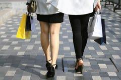 Låt ` s gå att shoppa, kvinnor som rymmer shoppingpåsar på gatan Arkivbilder