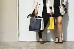Låt ` s gå att shoppa, kvinnor som rymmer shoppingpåsar på gatan Arkivfoto