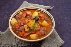Låta småkoka gjort med nötkött, bacon, korvpotatisar, morötter och örter Arkivfoton