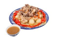 Låta småkoka med söt peppar för potatisar på en platta som isoleras på vitbac Fotografering för Bildbyråer