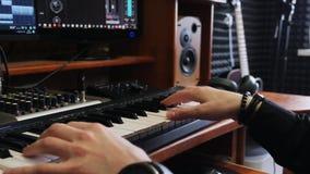 Låtskrivaremusikertekniker som spelar det midi tangentbordpianot i hem- anteckna studio med bildskärmar som blandar kugghjulet oc lager videofilmer