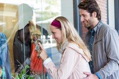 Lèche-vitrines allant de sourire de couples et pointage aux vêtements Photos libres de droits