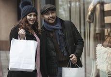 Lèche-vitrines de couples dehors en hiver Images stock