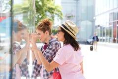 Lèche-vitrines femelle heureux d'amis dans la ville Image libre de droits