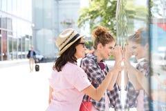Lèche-vitrines femelle heureux d'amis dans la ville Photo libre de droits