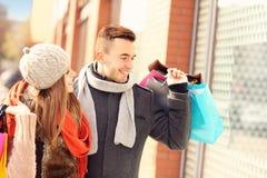 Lèche-vitrines heureux de couples dans la ville Photographie stock libre de droits