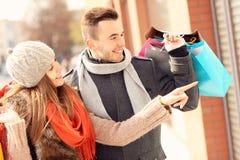 Lèche-vitrines heureux de couples dans la ville Images libres de droits