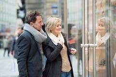 Lèche-vitrines supérieur de couples au centre de la ville L'hiver Image stock