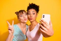 Lèvres drôles de voyage d'été de v-signe de photo d'étudiante de personnes de portrait les belles deux ont boudé le dessus-noeud  image stock