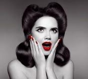 Lèvres et ongles manucurés rouges La goupille étonnée vers le haut de la fille tient des joues photo stock