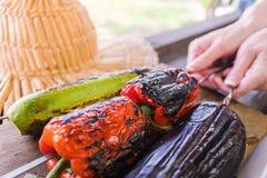 Légume grillé sur une casserole de gril Femme tenant une brochette avec les légumes grillés au-dessus d'une planche en bois Photos stock