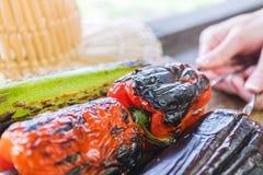 Légume grillé sur une casserole de gril Femme tenant une brochette avec les légumes grillés au-dessus d'une planche en bois Images stock