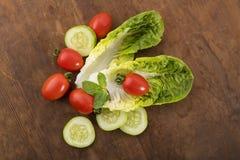 Légume : Romaine Lettuce verte fraîche avec des tomates de bébé, des feuilles en bon état et des tranches de concombre sur le fon Photo stock