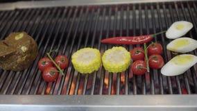 Légume sur le gril dans le plan rapproché de cuisine de restaurant Faites cuire griller le maïs, les tomates-cerises et le schéna banque de vidéos