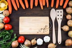 Légumes autour de planche à découper et des cuillères de cuisson Images stock