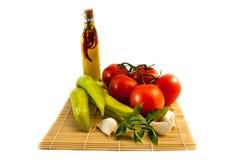 Légumes avec de l'huile ilive d'isolement sur le fond blanc Photographie stock libre de droits