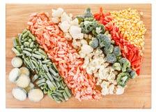 Légumes congelés mélangés sur la planche à découper Photos libres de droits