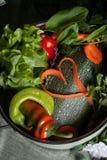 Légumes crus dans une casserole et des carottes de coeur, vegan Photos libres de droits