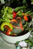 Légumes crus dans une casserole et des carottes de coeur, vegan Image libre de droits