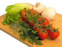 Légumes crus sur le panneau de découpage Image stock