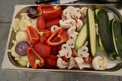 Légumes découpés en tranches crus sur un grand plateau, champignons, paprika, courgette, oignon Images libres de droits
