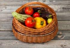 Légumes dans le panier sur la vieille table en bois Photo stock
