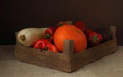 Légumes dans une boîte en bois sur un fond foncé Photos libres de droits