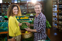Légumes de achat de couples heureux dans la section organique Photographie stock