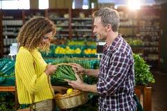 Légumes de achat de couples heureux dans la section organique Photo stock