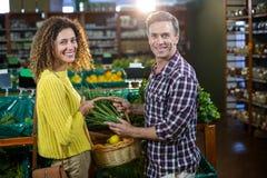 Légumes de achat de couples heureux dans la section organique Image libre de droits