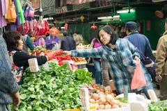 Légumes de achat de femme sur le marché en plein air, Hong Kong Photographie stock libre de droits