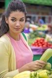 Légumes de achat de jolie jeune femme sur le marché Images stock